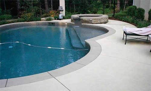 Radiant 18×32 Semi-Inground Freeform with walk-in steps, pavers and lights.